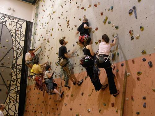 Des personnes vachées sur un mur d'escalade, en train d'apprendre les manipulations de corde.